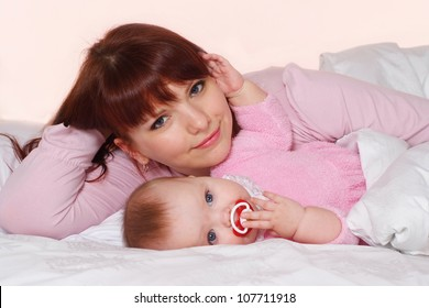 A pretty Caucasian mummy with her daughter lying in bed on a light background