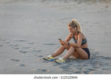 Pretty Caucasian sportswoman sitting on sandy beach and holding her cell phone.