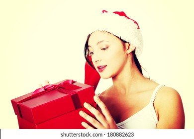 Pretty caucasian teen girl holding and looking at gift.