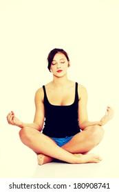 Pretty caucasian teen girl sitting on the floor and practising yoga.