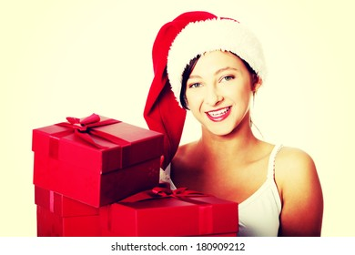 Pretty caucasian teen student in Santa`s hat holding gifts.