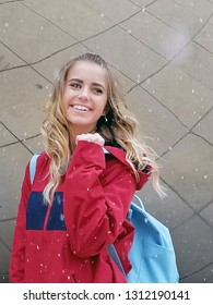 pretty Caucasian teenage girl with red jacket and blue backpack in snowflakes