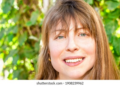 A pretty Caucasian woman with bang and unique blue eyes happily posing on the blurred background