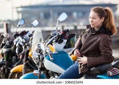 Pretty Caucasian woman biker sitting on motorbike, leather brown jacket and jeans, copyspace