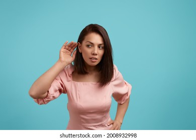 Pretty caucasian woman with dark hair wearing pink dress keeps hand near ear, tries to overhear private conversation, listens gossips, looks sideways,opens mouth, isolated on blue background