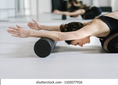 Pretty Caucasian woman doing pilates exercise on the floor with roller.