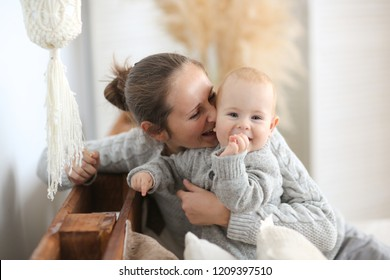 pretty caucasian woman kisses a charming baby in a gray knit sweater at home, living a real interior , Mom and son embrace, toning. Happy loving family.