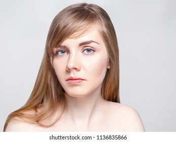 Pretty caucasian woman with long hair poses in studio, close up portrait