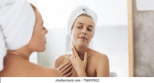 Pretty Caucasian woman looking her face in bathroom mirror.