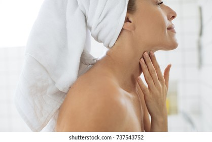 Pretty Caucasian woman with towel on her head touching her neck at bathroom.