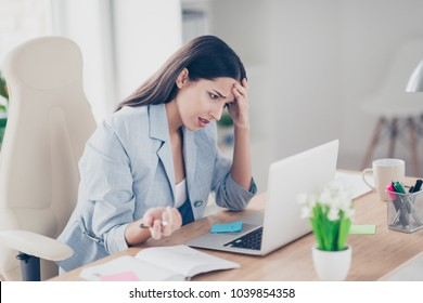 Pretty, charming, attractive, thoughtful woman tired from every day commonness, holding hand onforehead, looking bad, sitting on armchair at desktop in workstation, having a lot of work