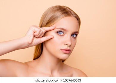 Pretty, charming, cute, nude, natural girl thinking about tightening, plastic operation, holding fingers near eyes, looking at camera isolated on beige background, wellbeing, wellness concept