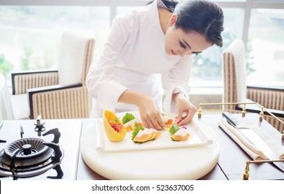 hübsche, elegante asiatische Küchenchef Dame Cook Dame bereiten französische Küche Mahlzeit, trendige Vogue verschwendete Girl-Modell in Koch-Uniform Küchenkleidung als Modeporträt