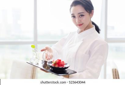 hübsche, elegante asiatische Küchenchefin Dame Cook Dame, die die Meeresfrüchte-Mahlzeit zeigt die französische Küche Mahlzeit, trendige Vogue verschwendete Girl-Modell in Koch-Uniform Küchenkleidung als Modeporträt