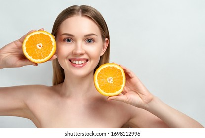 Pretty charming joyful attractive cheerful funny comic positive nude natural pure girl having two pieces of orange, on blue background. Skincare. Vitamin C. Blonde woman