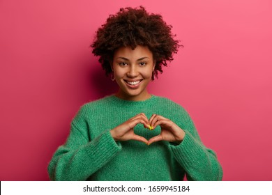 Pretty charming woman shapes heart gesture, shows what boyfriend mean to her, expresses affection and love, smiles pleasantly, wears green jumper, isolated over pink background. Body language concept