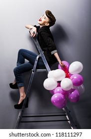Pretty cheerful fashion retro model teen girl laughing on ladder in studio with balloons