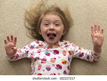 Pretty cheerful girl in pajama lying floor and having fun