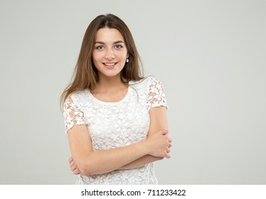 Pretty cheerful girl. Portrait happy woman on the gray background.
