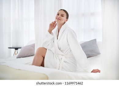 I am pretty. Cheerful girl in white soft bathrobe sitting on daybed at spa. She is touching face and looking at camera with smile