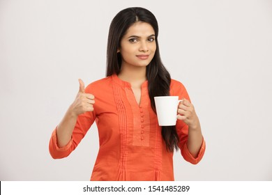 Pretty cheerful Indian young woman with coffee cup on white.