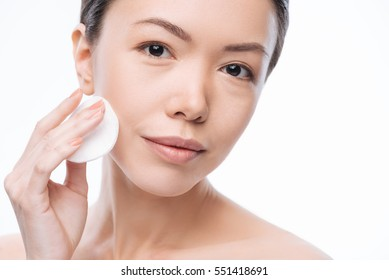 Pretty cheerful woman cleaning her face