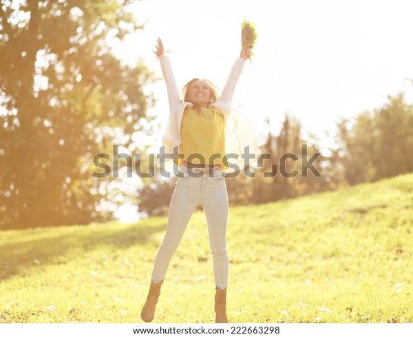 Pretty cheerful woman having fun in sunny autumn day