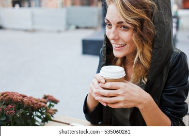 Pretty cheerful young blonde girl in smart casual eclectic outfit sits on cafe terrace while drinking coffee from paper cup. Coffee to go