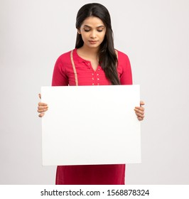 Pretty cheerful young Indian female holding white board.