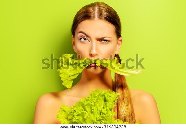 Giovane donna piuttosto allegra in posa con foglie di lattuga verde fresca. Un concetto di alimentazione sana. Dieta.