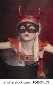 pretty child dressed as Halloween vampire with cauldron isolated on dark red  background