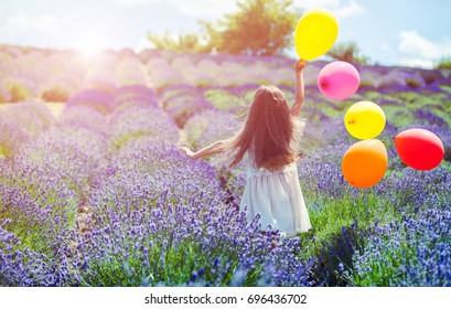 Pretty child girl runs with colorful balloons in lavender field, summer freedom concept