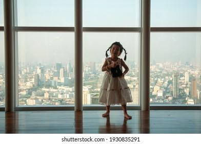 Pretty child looking through window.