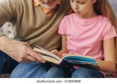 Pretty child reading story with grandparent