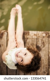Pretty child sitting on wooden surface.