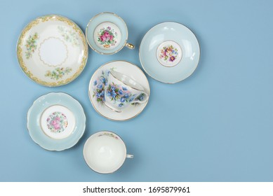 Pretty china teacups and saucers on blue background