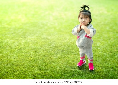 Pretty Chinese girl and happiness time. Cute Asian girl stand on green field. Adorable kid plays alone in the park