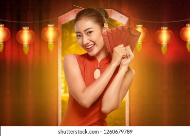 Pretty chinese woman with cheongsam dress holding red envelopes. Happy Chinese New Year