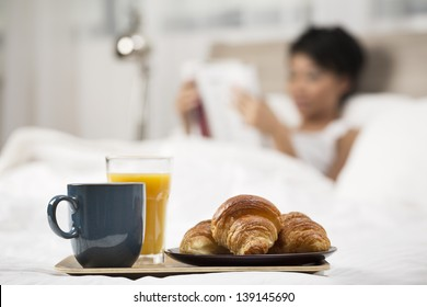 Pretty Chinese Woman having breakfast in bed