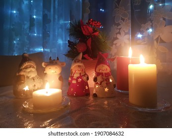 pretty Christmas figures and candles on the table