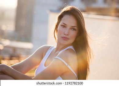 pretty city girl portrait at sunset backlight at top of building closeup