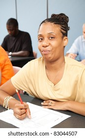 Pretty college student with Cerebral Palsy, taking a test in her adult education class.
