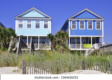 Pretty colorful beach homes as viewythrough the dunes.