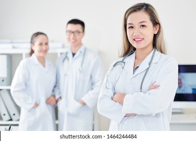Pretty confident young smiling Vietnamese general practitioner with stethoscope standing in front of her colleagues