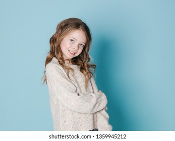 pretty and cool 9 year old girl with brown wool sweater posing in front of blue background
