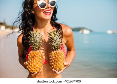 Pretty cool fashionable girl in the bright swimsuit, sunglasses, posing against the backdrop of the sea. The two hands holding a pineapple.