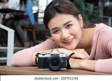 pretty cool young Asian woman with retro film camera or mirrorless camera in modern garden open mall.young woman holding mirrorless camera in vintage tone