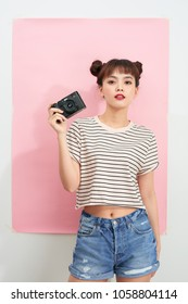 Pretty cool young asian woman model with camera over pink.