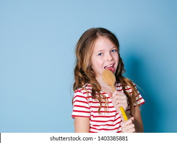 pretty cool and young girl uses cooking spoon as microphone and sings in front of blue background