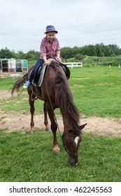 Pretty country girl sitting astride a brown horse, horse feeding green grass